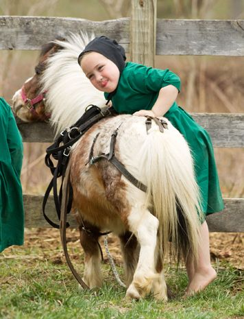 An Amish girl attempts to mount a miniature horse near the family farm in Bergholz, Ohio, April 9, 2013.