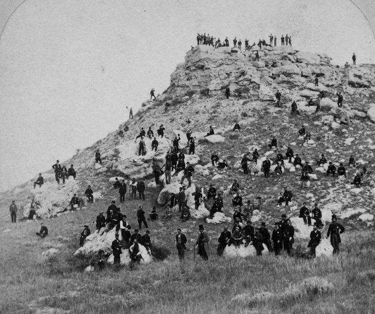 Stereoview of a large group of people, probably mostly journalists, posing on a rocky hill near the Union Pacific Railroad line in Pine Bluffs, Wyoming, 1868. By John Carbutt.