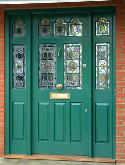 An emerald green front door with similar tones within the stained glass.
