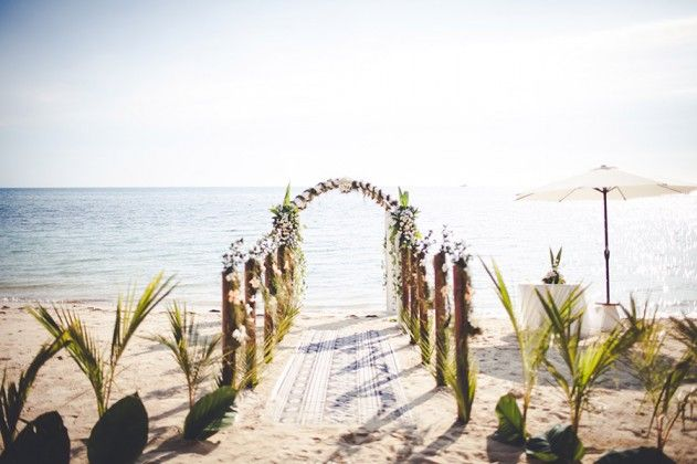 I like the use of peir-style wooden poles decorated with native ferns and greenery to create the aisle - not overly flowery ;-)  ..still not sold on the floral arch - four posters more my style (Lomani Resort, Mamanuca Islands, Fiji)