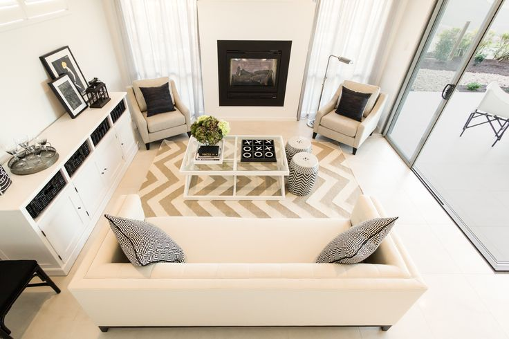 This light and airy family room features a two way fireplace with the alfresco. Layers of cream and taupe create a warm and inviting palette with pops of charcoal and chevron for depth and interest.