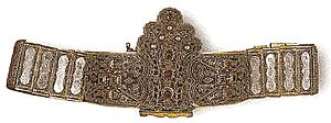 Gilded silver belt of articulated plates and integral buckle with floral ornaments in filigree, glass-paste 'gems' and enamel. Dimensions: 77 X 11.5cm.  1836. Athens, Byzantine Museum