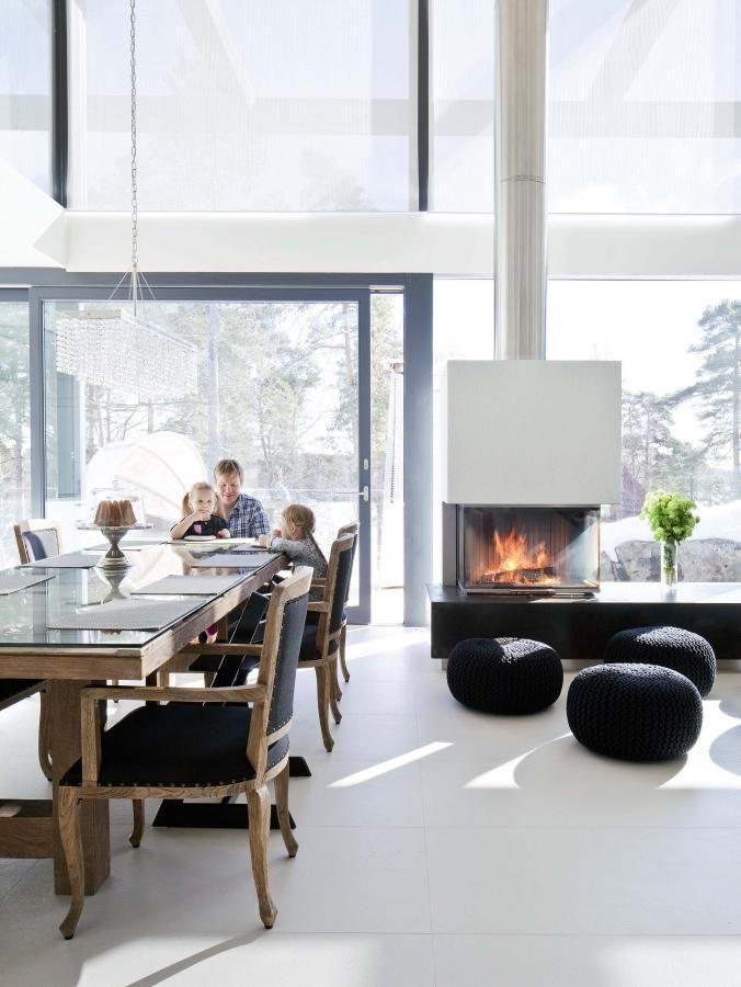 Kierrätystiikkipöytä ja tuolit ovat Jackpointista. Pöydän päällä Turun Kristallin käsintehty Boxi-kristallivalaisin. Olohuoneen takan on suunnitellut sisustusarkkitehti Esko Saarenoja ja toteuttanut Procat Brunnerin takkasydämellä. Mustat neulerahit ovat Luhta Homen. | Moderni kotisatama | Koti ja keittiö