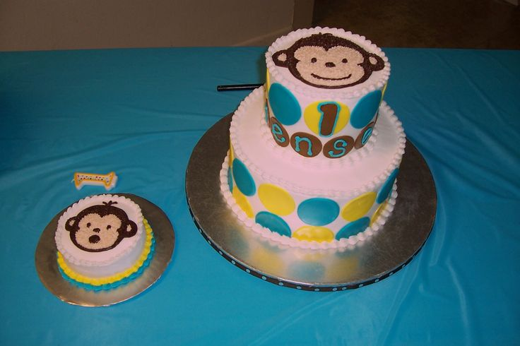 "Mod Monkey - 10 in. and 6 in. tiers.  Buttercream frosting and monkey.  Circles are fondant.  Brown circles have the letters ""Jensen"" (the birthday boy).  Smash cake is all BC.  Big hit at the little guy's party!"