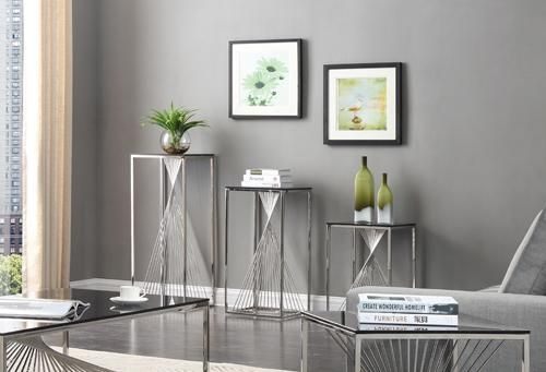 """Modrest Trinity Modern 3-Piece Glass & Stainless Steel End Table Set. The Modrest Trinity Modern 3-Piece Glass & Stainless Steel Table Set shows an artistic design featuring a sleek smoked tempered glass top with polished stainless steel base. The eye-catching twisted designed rod stainless steel situated between the top and base serve as accent. Available in large, medium, and small size, this modern steel table set requires some assembly. Dimensions  Large Table: W16"""" x D16"""" x H39""""  Medium…"""