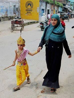 a Muslim woman walking her son who has dressed up as Hindu lord Krishna.  humanity is the greatest religion.