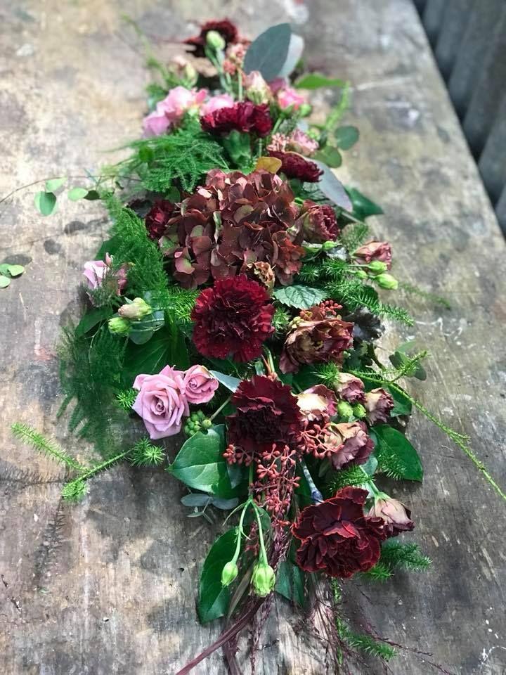 Matala syksyinen pöytäasetelma hortensiasta, ruususta, eustomasta, neilikasta ja erilaisista vihreistä.