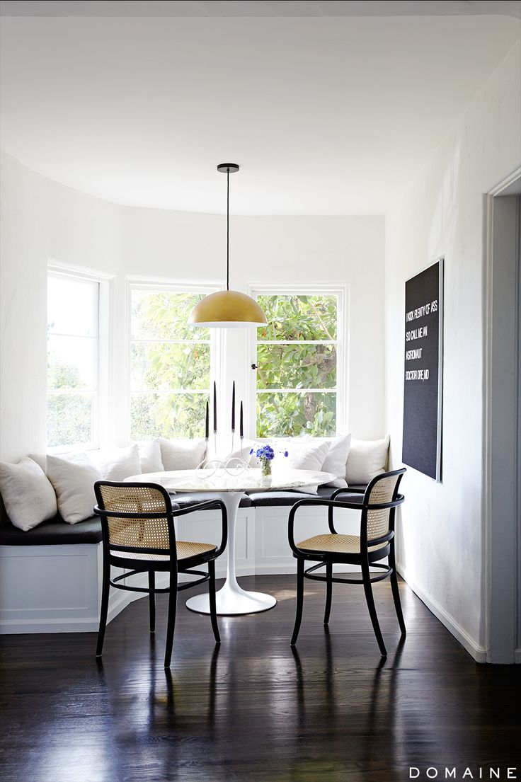 Bright breakfast nook with black and white artwork and modern chandelier