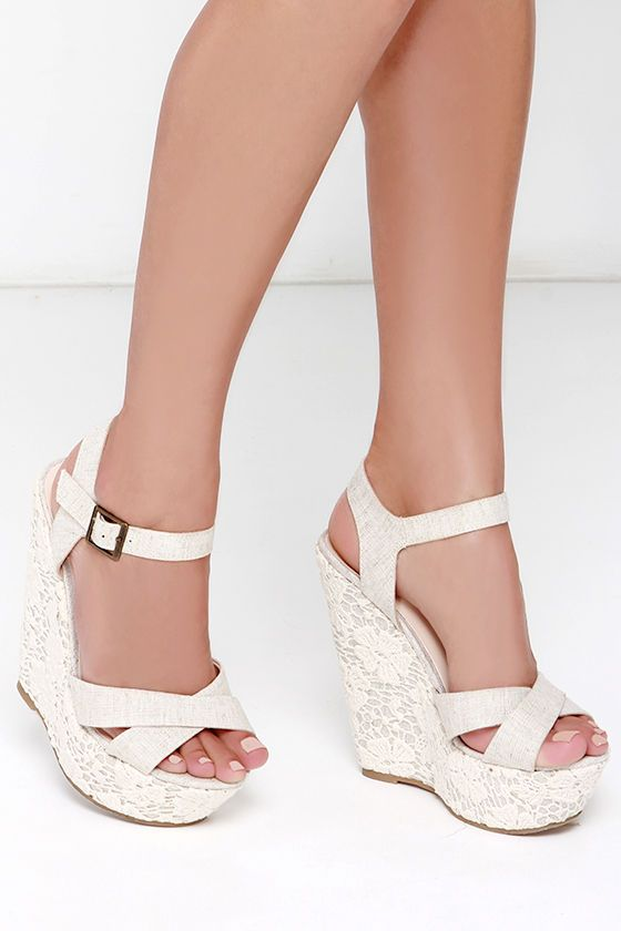 """We can spot a true romantic from a mile away, especially when she's loving her lace-covered Romantic Notions Beige Linen Lace Wedges! Crisscrossing fabric straps in light beige compose a peep toe upper, plus an adjustable quarter strap with brass buckle. Platform wedge heel revels in lace from the 5.75"""" heel to the 1.75"""" toe platform. Cushioned insole. Felted, nonskid rubber sole. Available in whole and half sizes. Measurements are for a size 6. All vegan friendly, man made materials."""