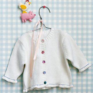 Gilet de bébé blanc avec boutons colorés et surpiqures blanches sur les manches et le bas
