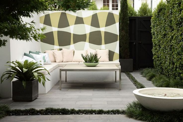 Minimalist modern landscape design with hedgerows and ornamental crops ard also fountains and modern minimalist furniture