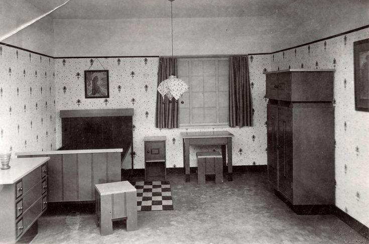 Huis inrichting. Inrichting van een eenvoudige slaapkamer in een modelwoning in Amsterdam. Links een houten bed, laden kast, houten krukjes, nachtkastje en een kleding kast. 1921.