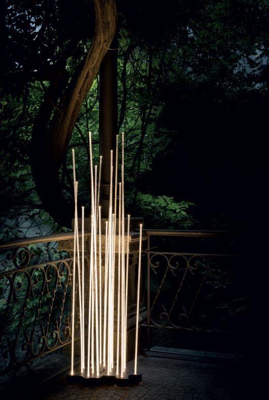 Illuminazione da esterno ARTEMIDE Reeds, design Klaus Begasse. Sette steli flessibili fungono da guida di luce ai LED posti alla base, creando una scenografica presenza luminosa. Materiali: base in alluminio verniciato, corpo della lampada in policarbonato trasparente