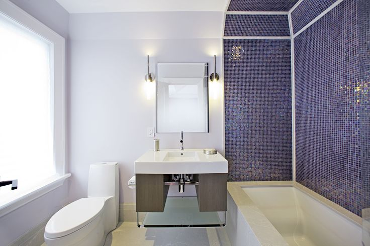 Fusing contemporary design with the warmness of a traditional century home, accented with iridescent blue-purple tile and a proper tub built in.