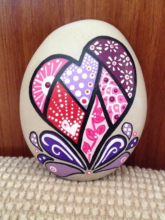 A symbol of your love or just a decorative piece to brighten up your desk, table, or someones day. This hand painted rock measures approximately 3.25x 2.75 x 1. Colors: Purple, Pink, Red, Sand, Black, White. Intended for indoor use; to avoid damage from prolonged exposure to outside elements. Protected with Satin Interior/Exterior Varnish. Water resistant. Clean with a damp cloth.