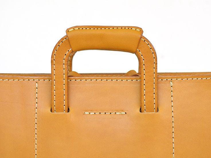 本体口はファスナー仕様、A4ファイルが十分収納できる大きさのビジネスバッグ。最大の特徴は取っ手が収納できることで、クラッチバッグのようにも持てるブリーフケースです。