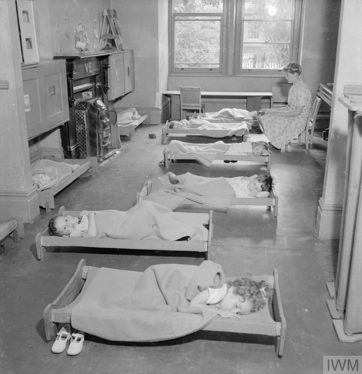 """A PICTURE OF A SOUTHERN TOWN: LIFE IN WARTIME READING, BERKSHIRE, ENGLAND, UK, 1945."""". """".© IWM (D 25267)IWM Non Commercial Licence  Young children enjoy an afternoon nap at the Pennsylvania Wartime Nursery, Reading. A female teacher can be seen in the background, keeping an eye on them as they sleep on small wooden cots. This nursery is funded by donations from Reading's sister town in the United States."""