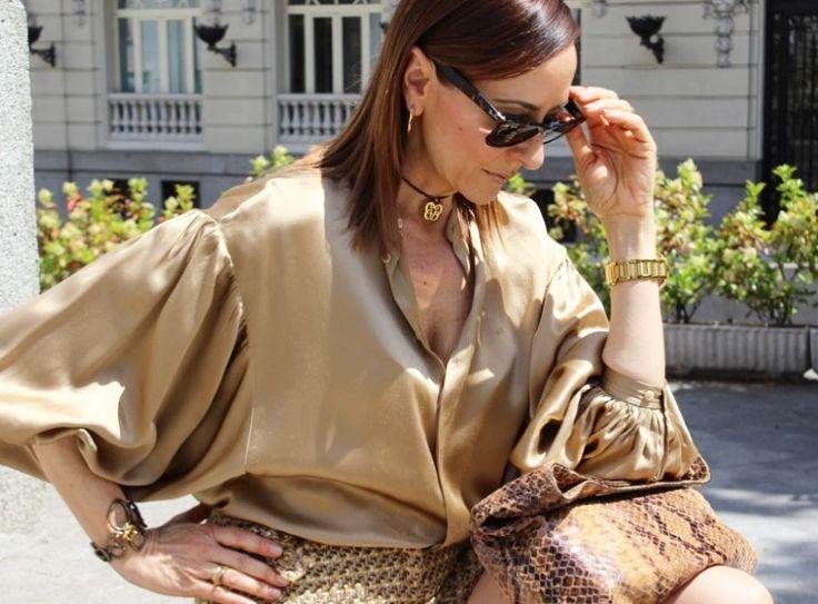 Camisa en dorado, melena ido, gafas en marron, complementos en dorado, pantalones cortos en tonos marrón y bolso de serpiente en tonos marrones