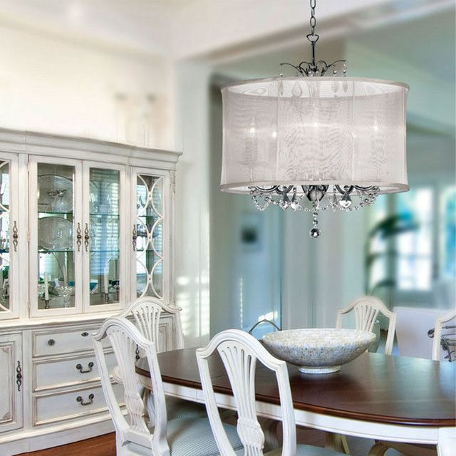 Contemporary Dining Room with Decoration Lighting Drum Shade Crystal Chandelier and Wooden Baste Oval Table with White Chair Beside Glass Cabinet Door and Drawers