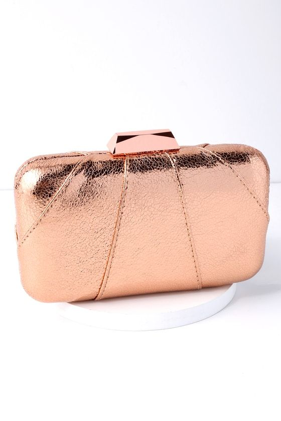 "The Katya Rose Gold Clutch is your next GNO's BFF! Crackled, metallic vegan leather covers this box clutch with a rose gold top clasp, and roomy interior, perfect for your night out essentials. Carry as a clutch or attach the 46"" long rose gold chain strap."