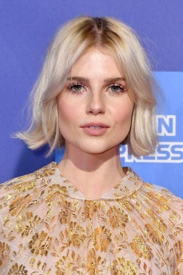 Hairstyles for thin hair: Lucy Boynton with her short platinum blonde hair styled into a short, flipped bob with Bardot bangs, wearing a floral top on...