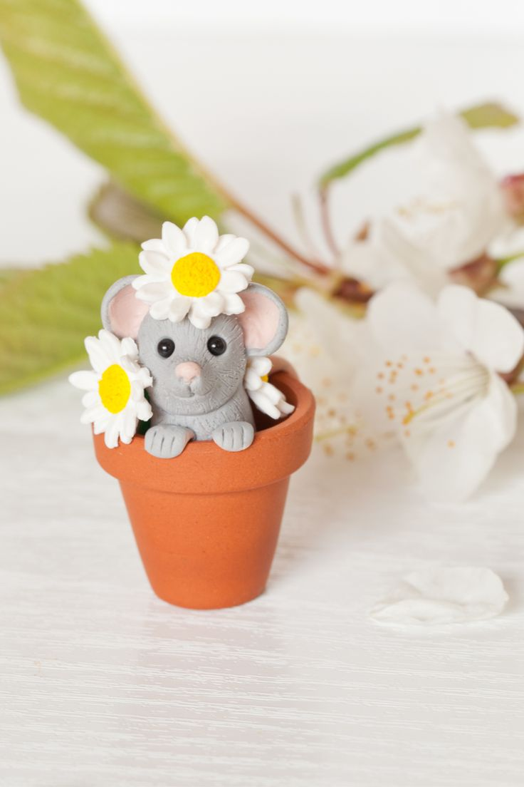 What a cute mouse popping it's head up with a cheeky smile while playing among daisies. Surrounded by individually handcrafted daisies the little mouse grasps the edge of the plant pot, smiling up at you while its tail curls out over the back.