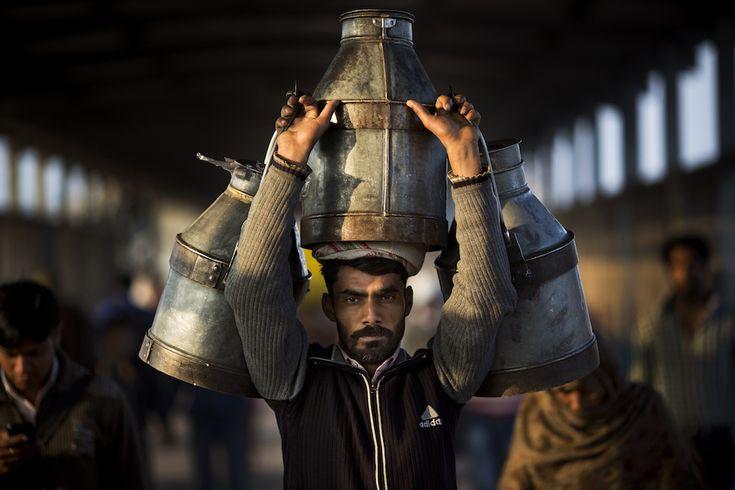 Un uomo indiano trasporta tre contenitori pieni di latte alla stazione ferroviaria di Ghaziabad, alla periferia di New Delhi, 24 febbraio (AP Photo/Bernat Armangue)