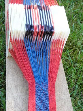 Weaving a copy of an Iron Age band -probably cuffs- from Brødbæk in Denmark using white and painted plastic tablets. Tablet woven by Lise Ræder Knudsen