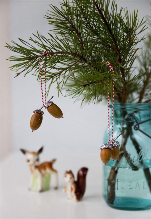 Låt julen glittra. Glittrande ekollon är perfekta pyntet till den lilla granen. För dig som inte får plats med en stor gran hemma är det också fint att sätta några tallkvistar i en vas.