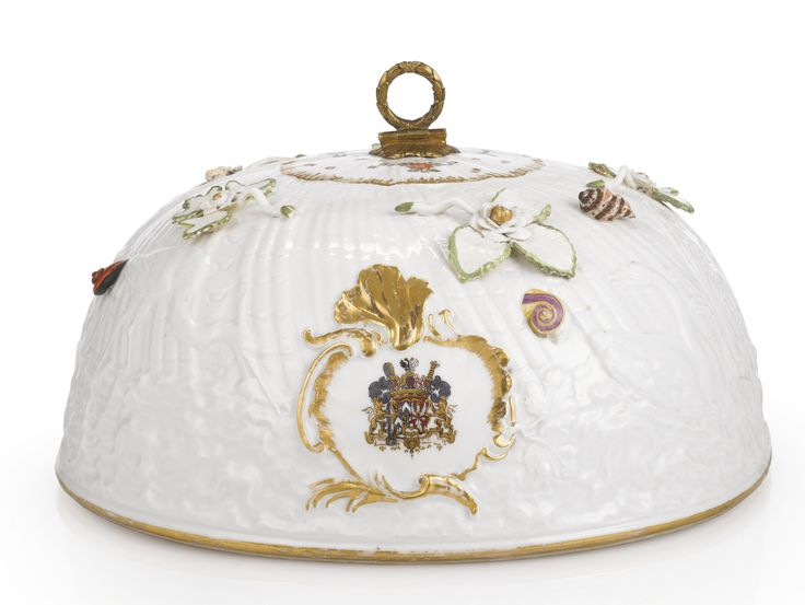 A MEISSEN 'WARMEGLOCKE' FROM THE SWAN SERVICE 1737-41 modelled by Johann Friedrich Eberlein, the domed cover molded in low relief with a crane in flight above two swans and a crane amidst waves and rushes against a ground of spirally radiating shell-work, on either side with the arms of Count von Brühl and his wife, Anna von Kolowrat-Krakowska, within a gilt cartouche, applied with shells and leafy flower sprigs, set with a gilt bronze handl