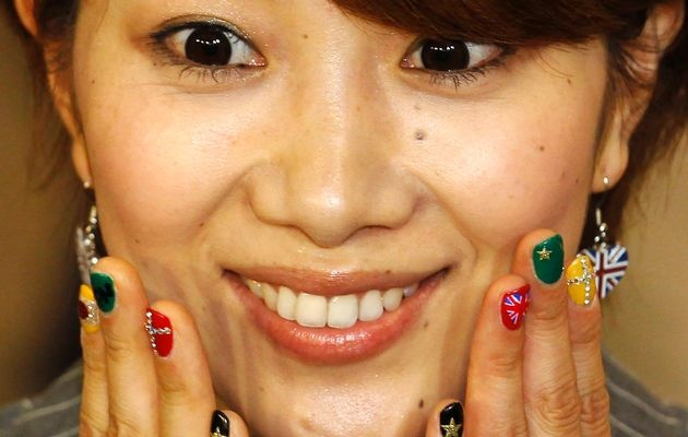 Badminton player Reiko Shiota shows off her brightly coloured nail polish with depictions of both the Japanese and the Union flags as she arrives with other memebrs of Japan's Olympic team and delegation for the London 2012 Olympic Games at Heathrow Airport in London July 22, 2012.