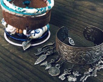 Set bracciale e braclet boho rustico unico.  Il polsino regolabile rustico è upcycled cuoio impreziosito da ricami e pizzo vintage. Il braccialetto di perline combina vintage rosa e bianco Hmong cuscino in tessuto, perle di osso - tra cui un cranio poco intagliato - afflitto e sfaccettate in vetro e un po ossidato argento Cherubino.  Il bracciale è regolabile da 6 1/2 pollici (16 1/2 cm) verso lalto usando i nastri di pizzo. Il braclet è circa 8 pollici (20 cm) alla fine e si chiude con un…