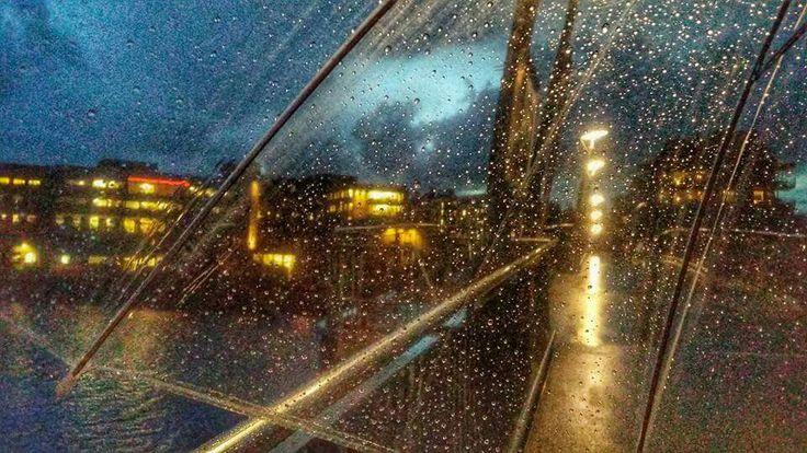 En regnfull kveld over gangbroa til Kaldnes, gjennom paraplyen min.