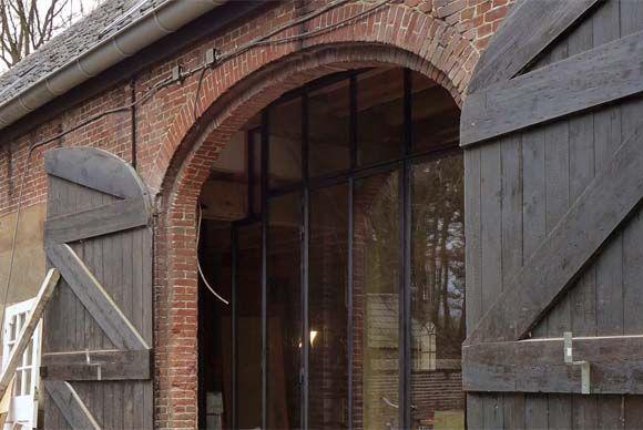 Stalen pui achter oude staldeuren