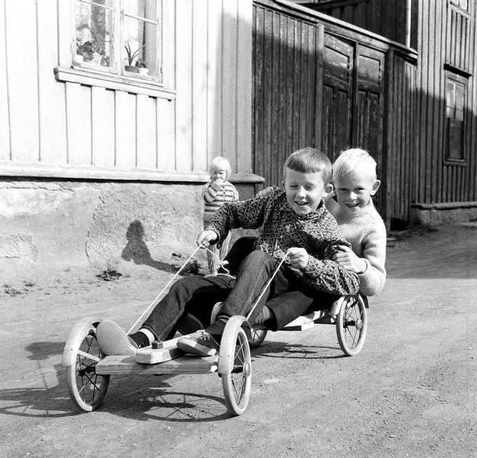 Olabil, - eller kanskje raggarbil? Dag Inge Antonsen fra Kirkegata hadde fått god hjelp av pappa med dette flotte kjøretøyet. Den blide passasjeren er Øyvind Halvorsen fra Bakkegata. Og som bildet viser har de allerede ei beundrende lita «rype». (Adresseavisen 13. august 1966)