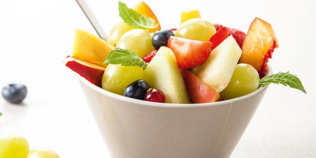 Een fruitsalade met witte druiven, Galia meloen, mango, nectarines, aardbeien, limoen, verse munt, rode bessen en blauwe bosbessen.