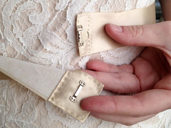 My wedding dress fit well off the rack, except it really needed some waist definition. So I bought a spool of 2″ wide polyester satin ribbon from Jo-Ann Fabrics and tied it into a sash. It pu…