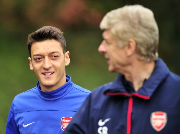 Arsenal's German midfielder Mesut Ozil (L) and French manager Arsene Wenger (R) speak during a team training session for the forthcoming UEFA Champions League Group F football match against SSC Napoli at Arsenal's London Colney training ground in north London on September 30, 2013. Arsenal will play against Napoli at the Emirates Stadium on October 1, 2013