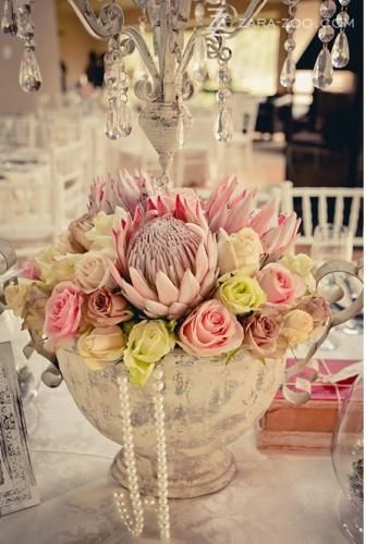 We loved working on this wedding. Proteas and roses were used. The pearls and crystal centerpieces worked very well with the flowers.