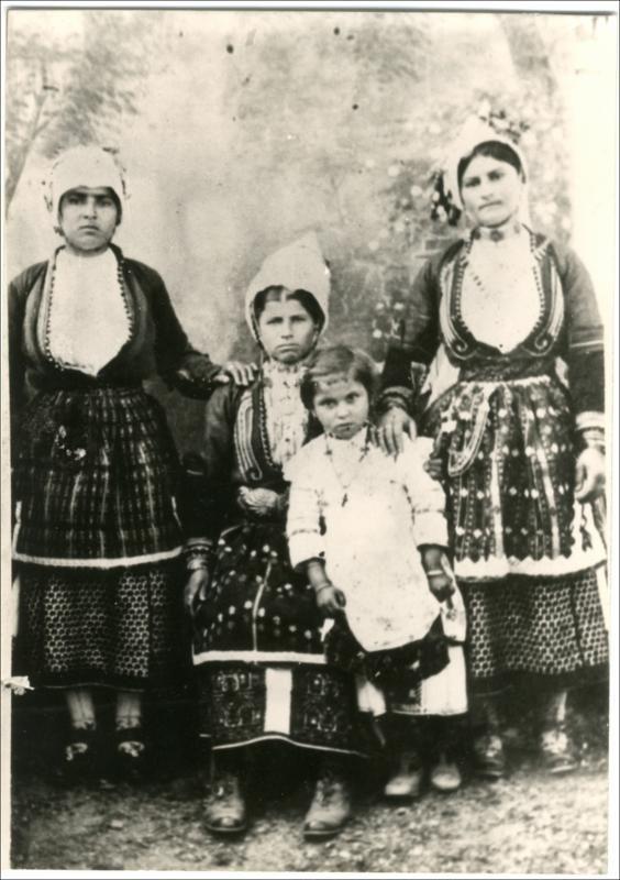 Οικογένεια με φορεσιές από τα χωριά του κάμπου της Ημαθίας: Χαρίεσσα, Αγ. Μαρίνα, Άγ. Γεώργιος, Κοπανός, Παλιό Ζερβοχώρι.  Ημερομηνία Έκδοσης: 1930. Συλλογή Χρυσάνθης Κωστοπούλου, Ημαθία. Δημόσια Κεντρική Βιβλιοθήκη της Βέροιας