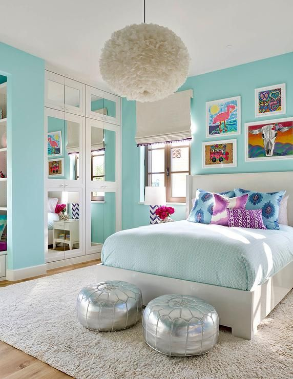Turquoise blue girls bedroom features a white feather chandelier, Eos White Pendant, illuminating a white wingback bed dressed in pale blue bedding as well as blue and purple paisley pillows tucked under an eclectic art gallery placed next to casement windows covered in a white roman shade accented with purple tassel trim.