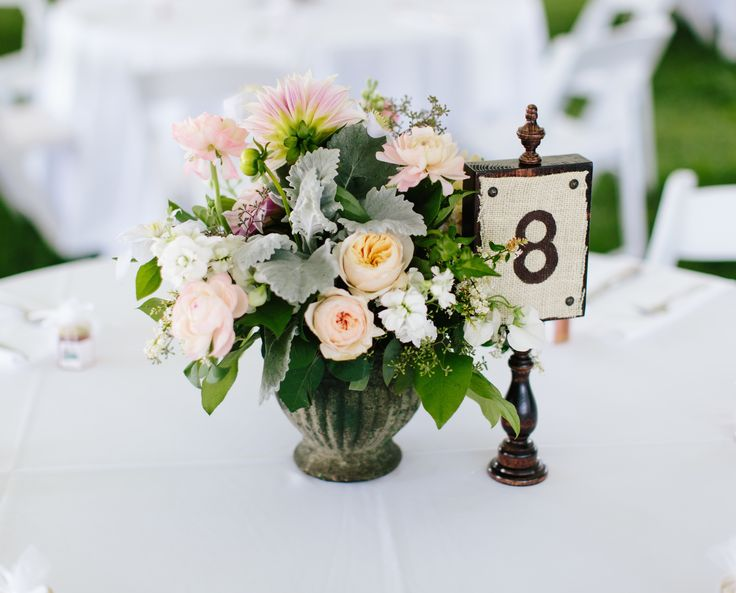 garden inspired table arrangement for an outdoor wedding reception of white clematis, peach cafe au lait dahlia, peach garden rose, white stock, pink ranunculus, seeded eucalyptus and dusty miller in a mossed concrete urn.