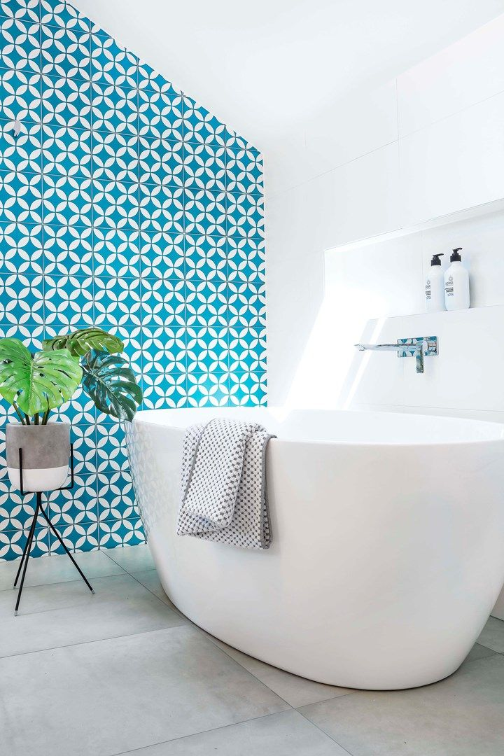 The ensuite is now a sunny haven with hotel-worthy detailing, including a sumptuous freestanding bath and a bold feature wall of teal-patterned tiling that elevates the room to a style show stopper | Home Beautiful magazine Australia
