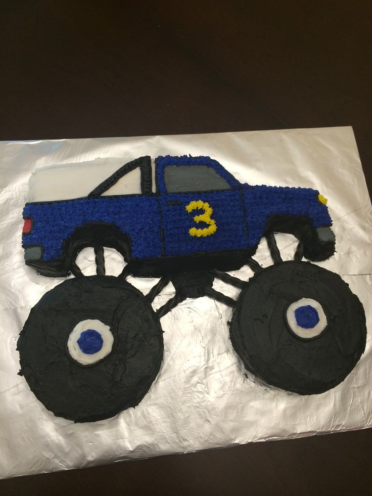 """Monster Truck Birthday Cake - Used a Wilton 1980s truck cake pan that I rented from a cake supply store. I cut out the tires and added my own using 6"""" pans then decorated. I used black licorice to connect the wheels to the cab. My 3 year old loved it!"""