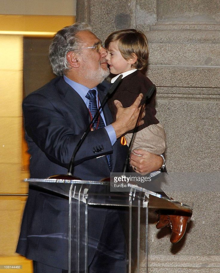 Spanish tenor Placido Domingo (2nd-L), carrying his grandson in his arms, is awarded with Order of Arts and Letters by Spanish Culture Minister Angeles Gonzalez-Sinde at Prado Museum on January 18, 2011 in Madrid, Spain.