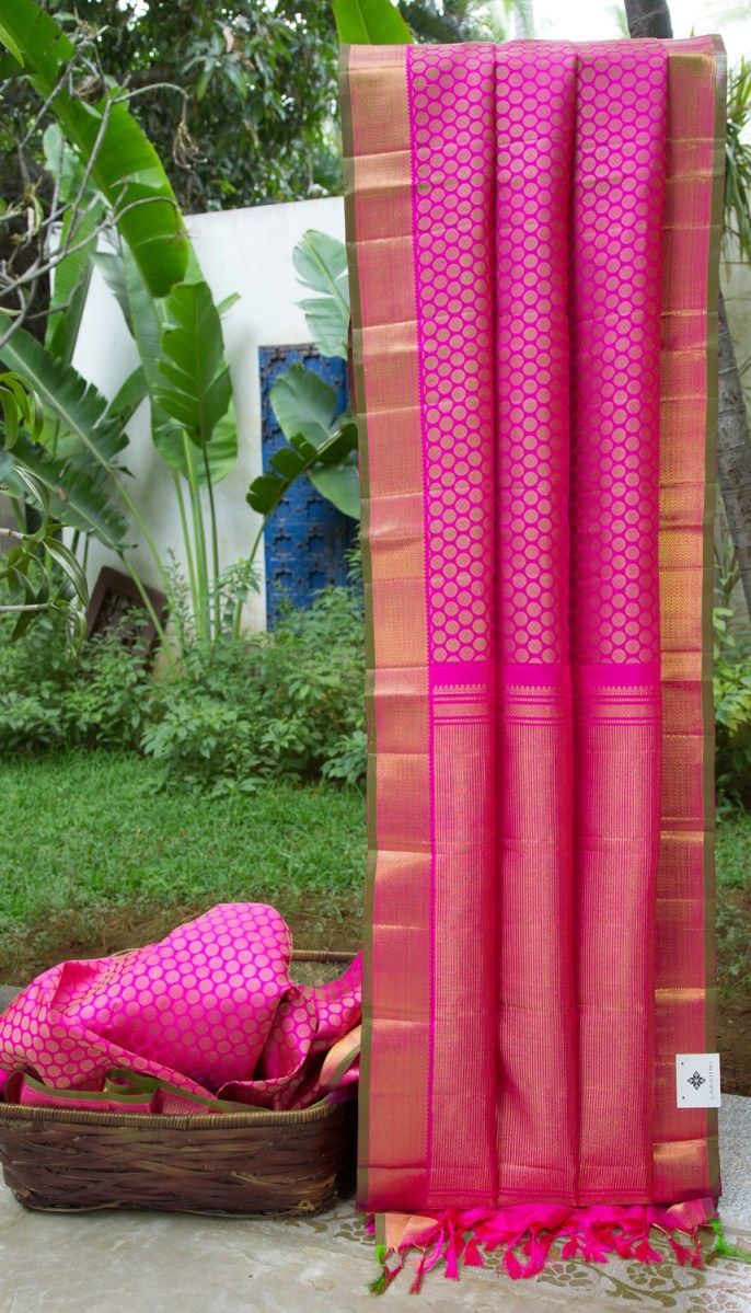 This iridescent magenta kanchivaram silk has bhuttas in beige all over. The herringbone gold border is finished by a striking textured pallu