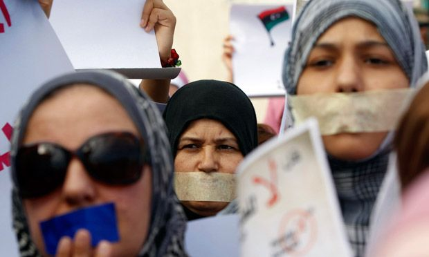 Libyan women - Silent protest … demonstrators with taped mouths take part in a march supporting women raped during the war in Libya. Photograph: Mohamed Salem/Reuters
