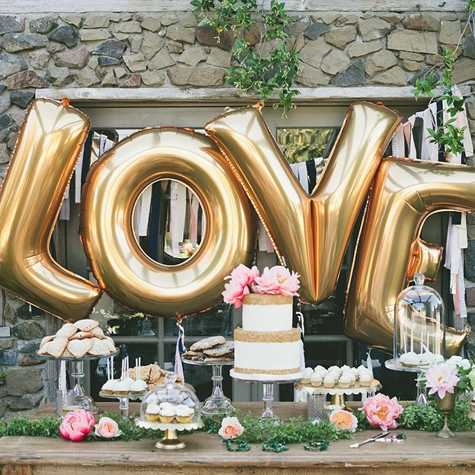 Brides.com: . A gold-dusted dessert bar with a two-tiered wedding cake, cupcakes, and gold letter balloons.