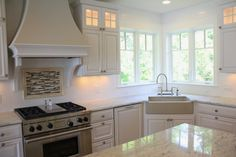 """Lovely White classic kitchen with unique corner apron sink layout.. Dishwasher to the left of the sink is """"hidden"""" with a cabinet front. Stainless steel range and curved decorative hood continue the fresh lo"""