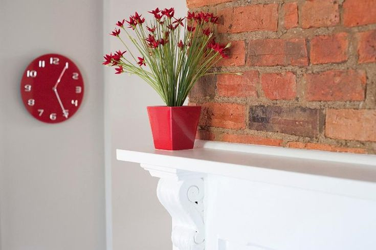 Decorative red flowers in a rustic lounge standing on a cupboard against a face brick wall with a stylish red clock on the wall alongside - free stock photo from www.freeimages.co.uk
